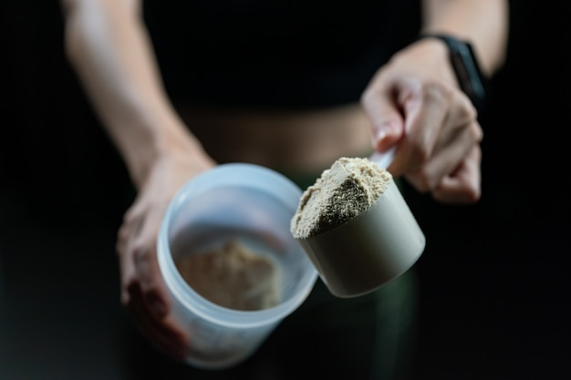 Close up of women with measuring scoop of whey protein and shaker bottle, preparing protein shake.