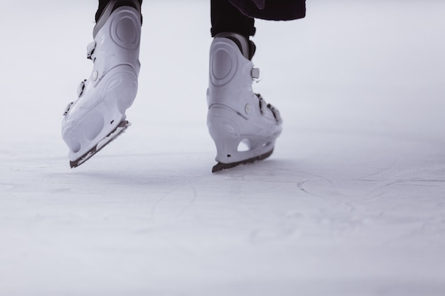 Close-up of womens legs on skates in winter on an open skating rink, place for text