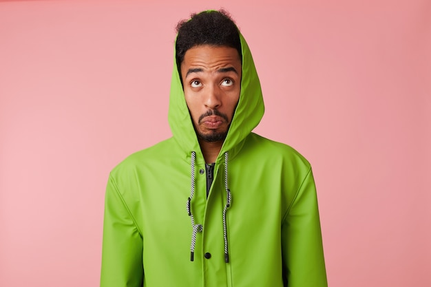 Close up of wondered young african american handsome guy in green rain coat, looks up in confused, clenched lips, stands.