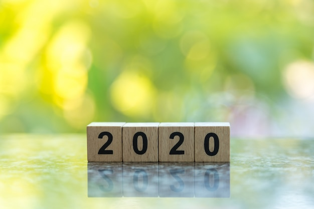 Close up of wooden 2020 number block toy on ground with bokeh green leaf nature
