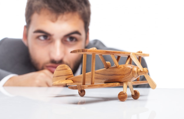 Close-up of wooden airplane with blurred businessman background