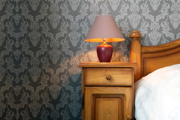 Close up of a wooden bed with white sheets and a cozy lamp, pattern wallpaper retro design.