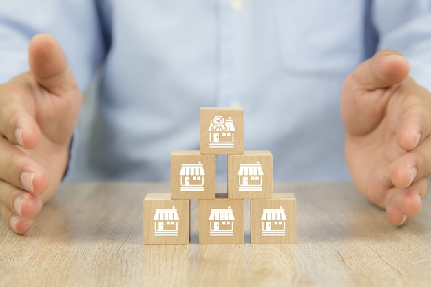 Close-up wooden block stack in pyramid with franchises store icon