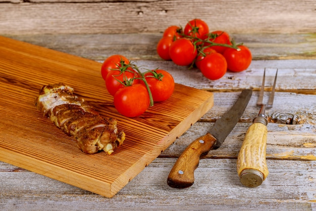 Close up on wooden board with grilled pork steak next to cherry tomatoes on wooden table