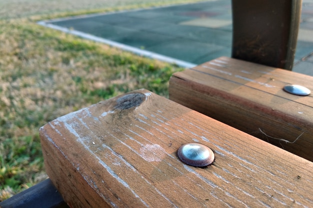 Close-up of wooden boards fastened with metal nails on a bench outdoors.
