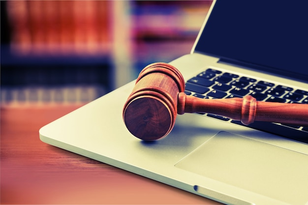 Close up of wooden brown gavel on laptop