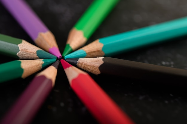 Close-up, wooden crayons arranged in a color wheel.