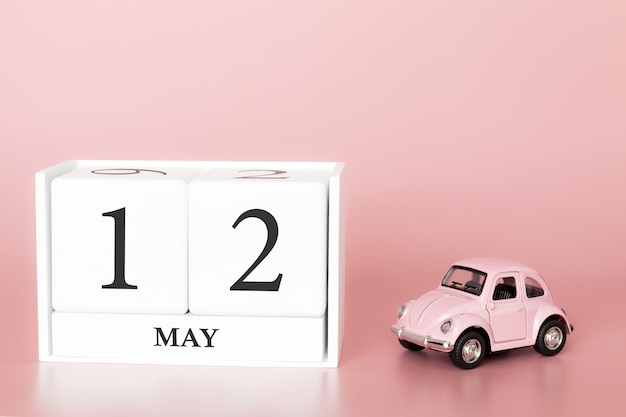 Close-up wooden cube 12th of may. day 12 of may month, calendar on a pink background with retro car.