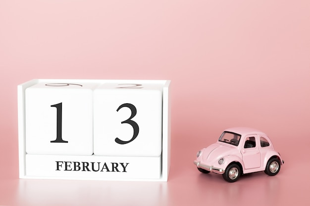 Close-up wooden cube 13th of february. day 13 of february month, calendar on a pink with retro car.