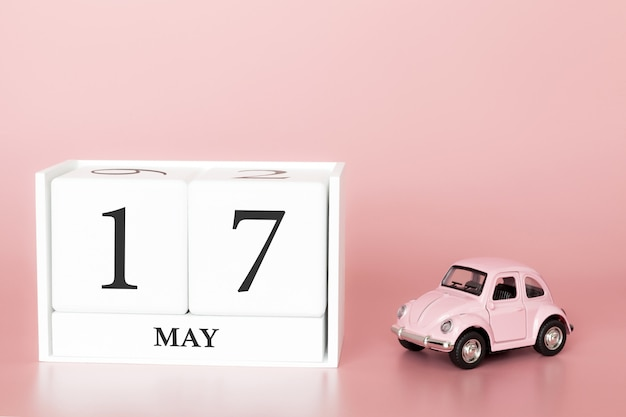 Close-up wooden cube 17th of may. day 17 of may month, calendar on a pink background with retro car.