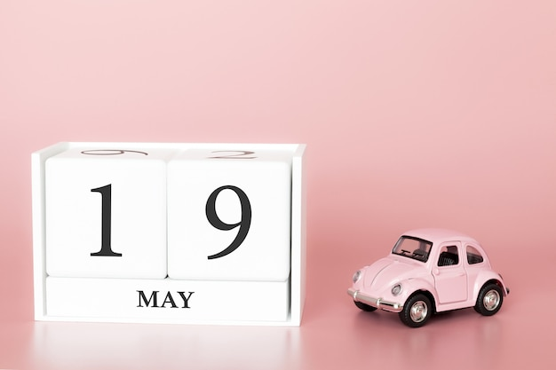 Close-up wooden cube 19th of may. day 19 of may month, calendar on a pink background with retro car.