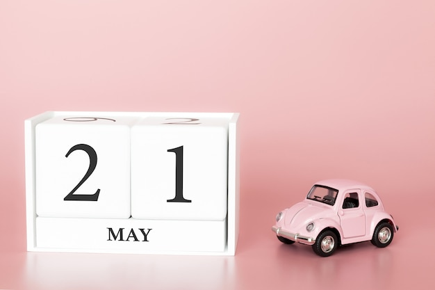 Close-up wooden cube 21st of may. day 21 of may month, calendar on a pink background with retro car.