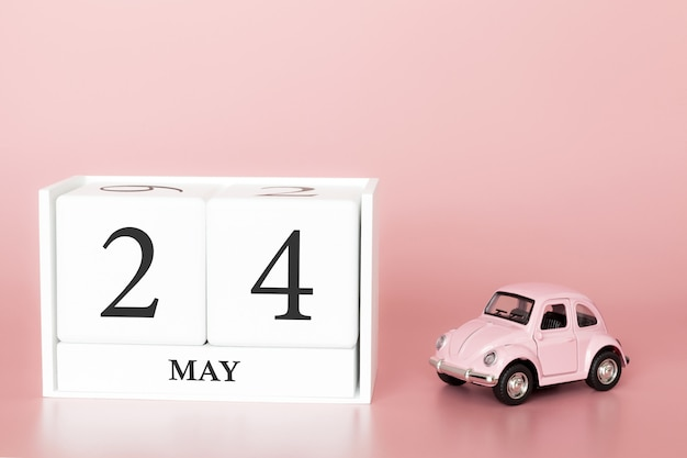 Close-up wooden cube 24th of may. day 24 of may month, calendar on a pink background with retro car.