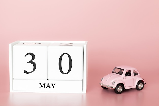 Close-up wooden cube 30th of may. day 30 of may month, calendar on a pink background with retro car.