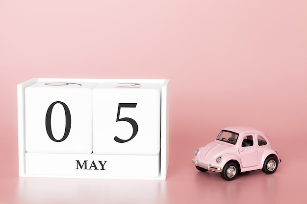Close-up wooden cube 5th of may. day 5 of may month, calendar on a pink background with retro car.