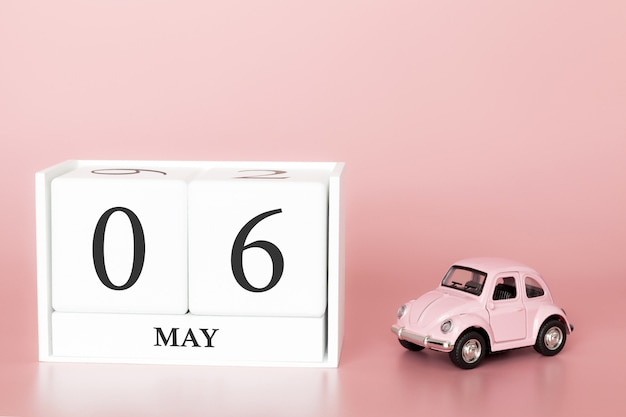 Close-up wooden cube 6th of may. day 6 of may month, calendar on a pink background with retro car.
