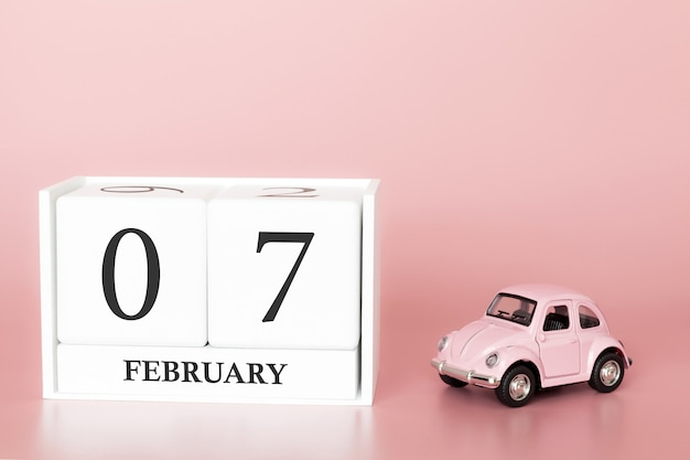 Close-up wooden cube 7th of february. day 7 of february month, calendar on a pink with retro car.