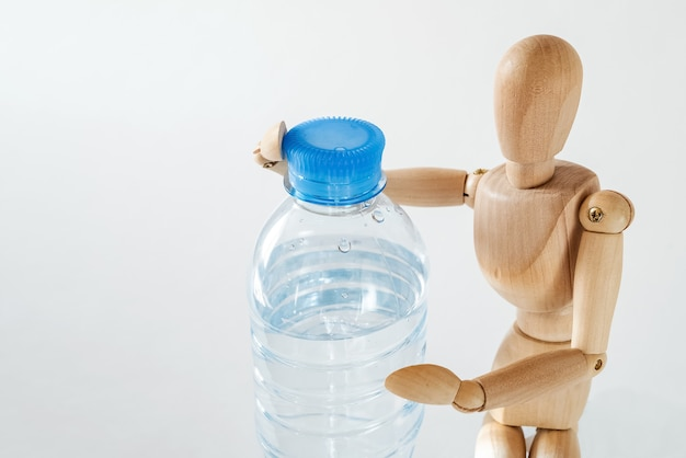 Close up of wooden dummy holds plastic bottle with water. drinking water, healthy life