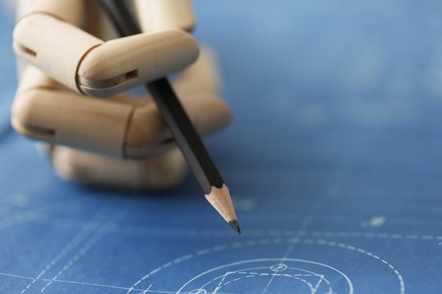 クローズアップの木製の手は、図の上に鉛筆を持っています。ロボット工学、製造における人工知能