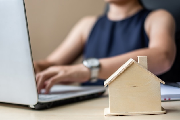 Close up wooden house model, businesswoman using laptop