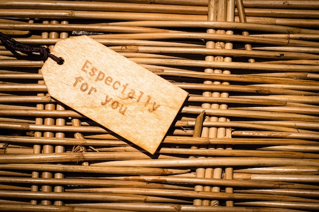 Close up of a wooden label with ribbon on wooden background