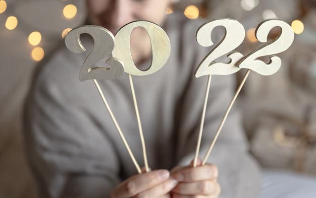 Primo piano di numeri in legno 2022 su bastoncini in mani femminili su sfondo sfocato con bokeh.