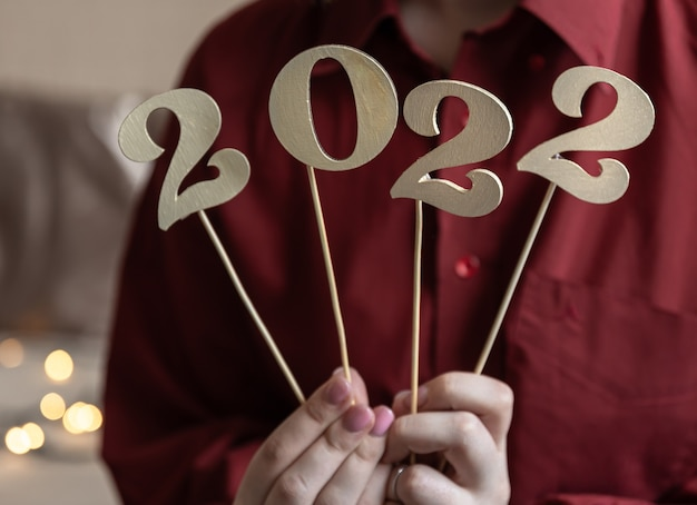 Close-up of wooden numbers 2022 on sticks in the hands of a girl, on a blurred background.