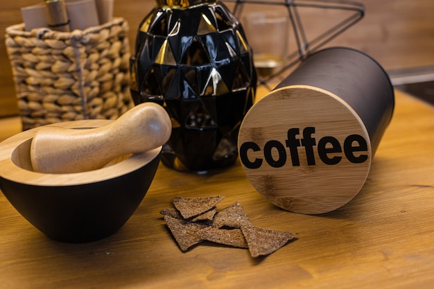 Close-up of wooden rustic mortar with pestle, container with coffee word on lid and healthy crackers on wooden kitchen counter.