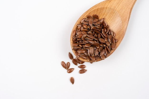 Close up of wooden spoon of flax seeds on a white background brown flax seeds in wooden spoon