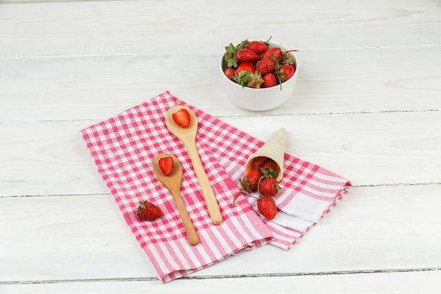 クローズアップの木のスプーンと白い木の板の表面にイチゴのボウルと赤いギンガムチェックのテーブルクロスにイチゴのコーン。水平
