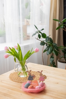 Close-up of wooden table with pink easter nest with colorful eggs and happy easter card, tulips in pitcher on napkin