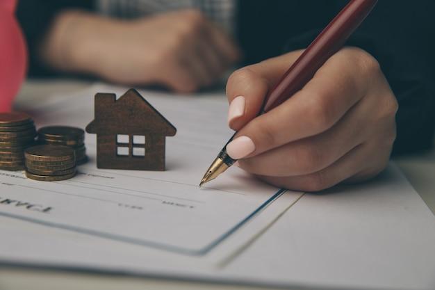 여자와 나무 장난감 집을 닫습니다 구매 계약 또는 주택, 부동산 개념에 대 한 모기지에 서명합니다.