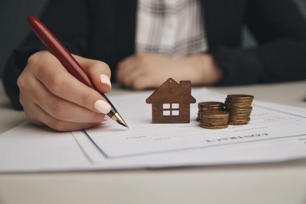 Крупным планом деревянный игрушечный домик с женщиной подписывает договор купли-продажи или ипотеку для дома