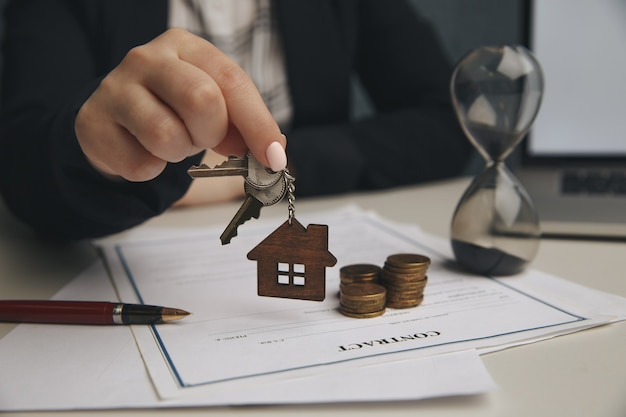 Close up wooden toy house with woman signs a purchase contract or mortgage for a home