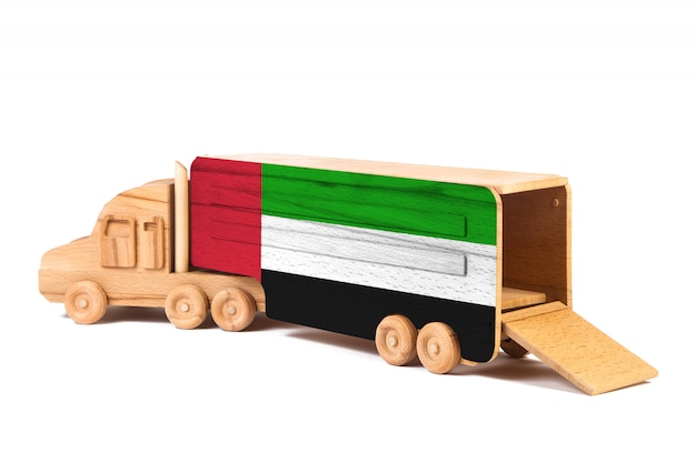 Close-up of a wooden toy truck with a painted national flag united arab emirates. the concept of export and import, transportation, national delivery of goods