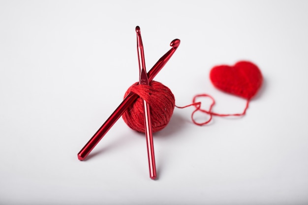 Close up of a wool ball and heart shape isolated