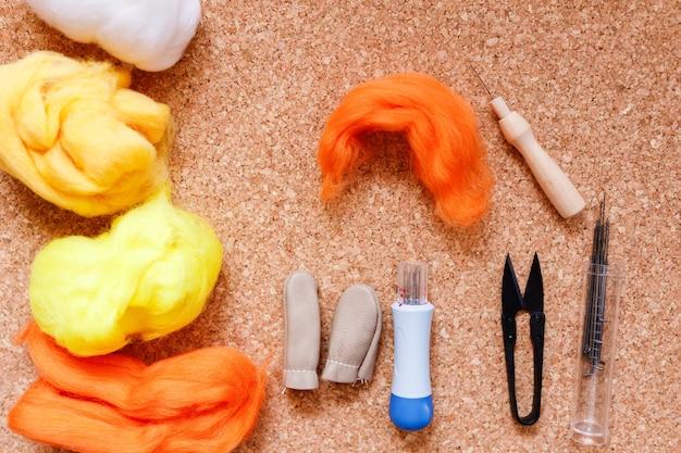 Close up of wool needle felting kit on cork surface.