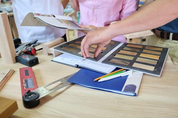 大工家具のワークショップでのクローズアップ作業、木材サンプルを持った労働者の手。