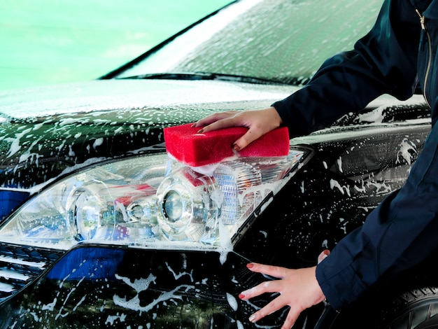 Close up worker asian woman hands washing in front of car with foam at garage.