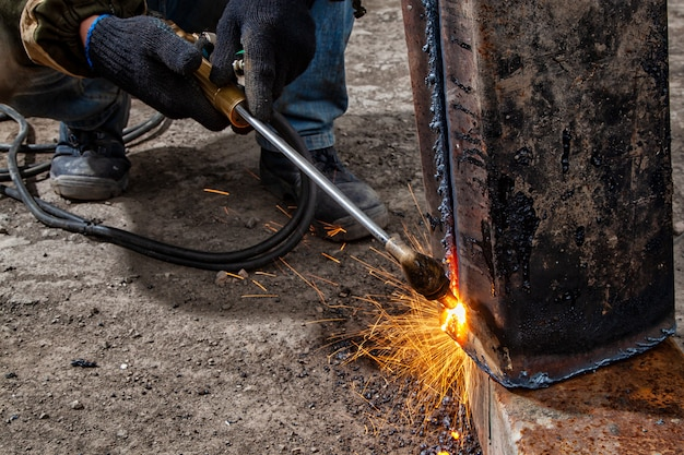 Close up worker cutting metal with gas