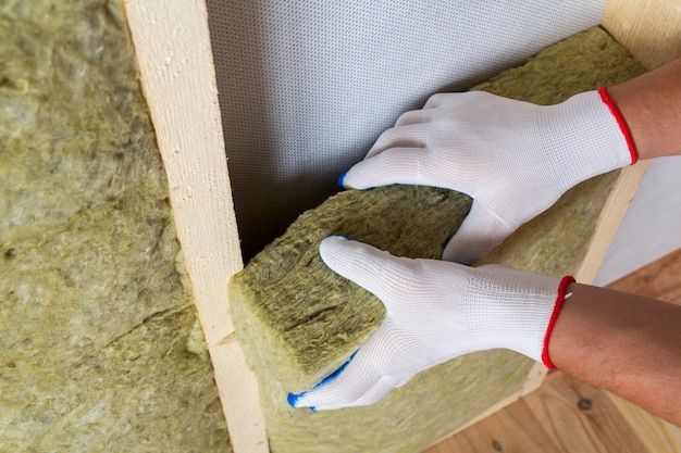 Close-up of worker hands in white gloves insulating rock wool insulation staff in wooden frame for future walls for cold barrier. comfortable warm home, economy, construction and renovation concept.