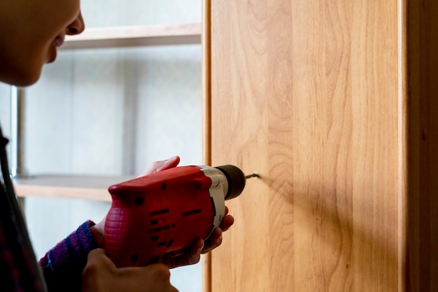 Close up worker making a hole in wooden surface at home using drill f