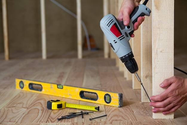 Close-up of worker's hands with screwdriver on background of professional tools and wooden frame for future wall in unfinished attic room under reconstruction. renovation and improvement concept.