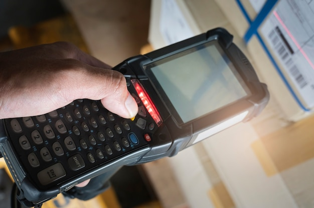 Close-up worker scanning barcode scanner with cargo shipment