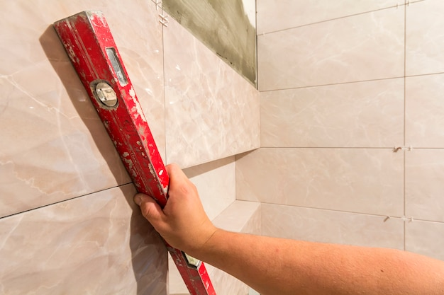 Close-up of worker tiler hand with lever installing on walls ceramic tiles.