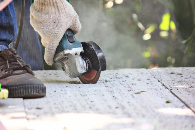 분쇄기를 사용하여 작업자를 닫고 시멘트 바닥에 구멍을 만드십시오.
