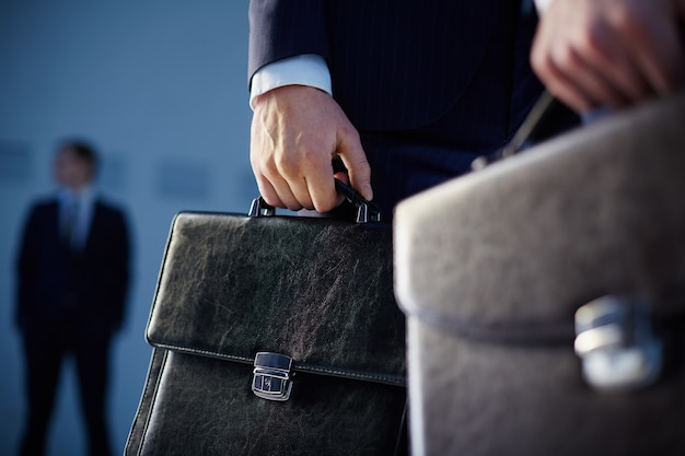 Close-up of workers with briefcases