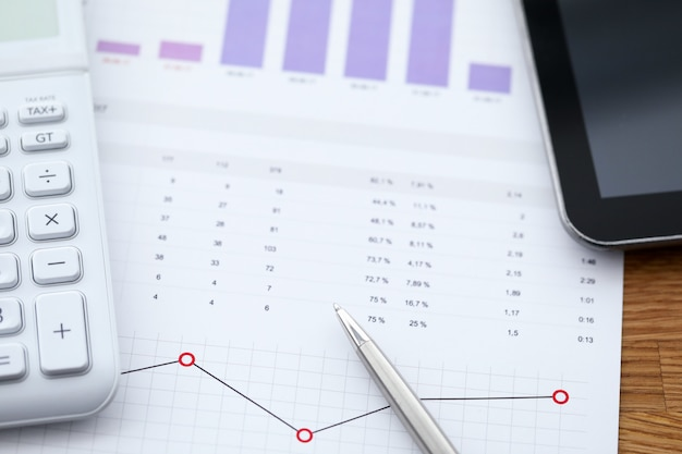 Close-up of workplace with business graphs and charts. data analysis and calculator on table. company expenses results and income. paperwork and office concept