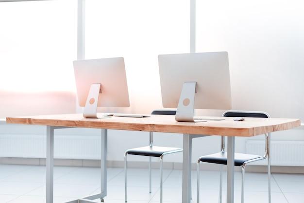 閉じる。空のオフィスのテーブルにコンピューターがある職場。