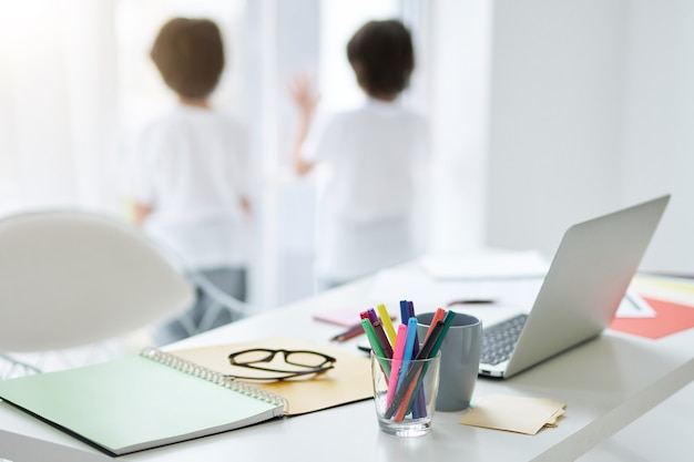 Close up of workplace with laptop, sticky notes and cup of tea on the table at home. two little children standing near the window in the background. distance education, home schooling concept